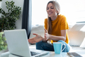 Smiling young blonde woman having videocall on laptop sitting on the couch - PhotoDune Item for Sale