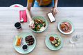 Young woman eating healthy food while using her mobile phone at home. - PhotoDune Item for Sale