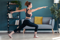 Attractive sporty young woman doing hypopressive exercises in living room at home. - PhotoDune Item for Sale