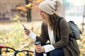 Beauty woman using her smart phone while drinking coffee sitting on a bench in the park in autumn. - PhotoDune Item for Sale