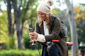 Beautiful woman sending messages with her smart phone while cycling through the park in autumn. - PhotoDune Item for Sale
