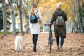 Two friends walking and cycling in the park while they going with their dog in the park in autumn. - PhotoDune Item for Sale