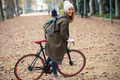 Pretty funny woman with a vintage bike enjoying time while cycling through the park in autumn. - PhotoDune Item for Sale