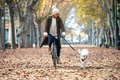 Beautiful young girl riding a bike while walking her dog in the park in autumn. - PhotoDune Item for Sale