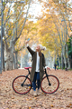Beautiful young woman taking selfie with her smart phone while cycling through the park in autumn. - PhotoDune Item for Sale