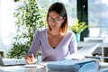 Young business woman working with calculator while consulting some documents in the office at home. - PhotoDune Item for Sale