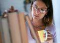 Smart young woman drinking a cup of coffee while looking for a book in the library at home. - PhotoDune Item for Sale