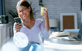 Beautiful young woman using her smart phone while drinking coffe in the office at home. - PhotoDune Item for Sale