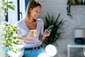 Beautiful woman using her mobile phone while drinking coffee standing next to the window at home. - PhotoDune Item for Sale