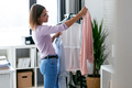 Beautiful young woman looking and choosing outfit at home wardrobe. - PhotoDune Item for Sale