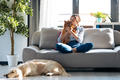 Attractive woman kissing her little cute dog while sitting in couch with her dogs and cat at home. - PhotoDune Item for Sale
