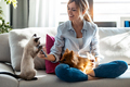 Beautiful woman playing with her cute dog and cat while using mobile phone sitting on couch at home. - PhotoDune Item for Sale