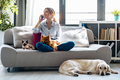 Pretty young woman talking with mobile phone while sitting in couch with her dogs and cat at home. - PhotoDune Item for Sale
