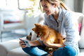 Pretty woman with her cute dog using mobile phone while sitting on couch in living room at home. - PhotoDune Item for Sale