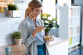 Beautiful young woman using her mobile phone while having healthy breakfast in the kitchen at home. - PhotoDune Item for Sale