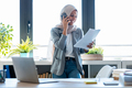 Muslim business woman wearing hijab talking with her smart phone while holding papers in the office. - PhotoDune Item for Sale