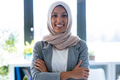 Smiling young muslim business woman wearing hijab looking at camera while standing up in the office. - PhotoDune Item for Sale