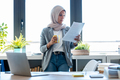 Beauty muslim business woman wearing hijab using her smart phone while holding papers in the office. - PhotoDune Item for Sale