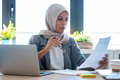 Confident young arabic business woman wearing hijab while working with laptop sitting in the office. - PhotoDune Item for Sale