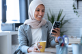 Beauty muslim business woman wearing hijab sending messages with mobile phone sitting in the office. - PhotoDune Item for Sale