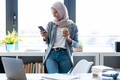 Muslim business woman wearing hijab using her smart phone while standing near window in the office. - PhotoDune Item for Sale