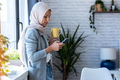 Beauty muslim business woman wearing hijab using mobile phone standing near window in the office. - PhotoDune Item for Sale