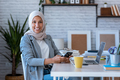 Beauty muslim business woman wearing hijab using her mobile phone while sitting in the office. - PhotoDune Item for Sale