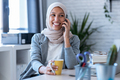 Smiling young muslim business woman wearing hijab talking with mobile phone sitting in the office. - PhotoDune Item for Sale