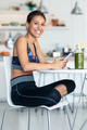 Sporty young woman using her mobile phone after session of exercises at home. - PhotoDune Item for Sale