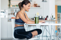 Sporty young woman working with her laptop after session of exercises in the kitchen at home. - PhotoDune Item for Sale