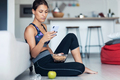 Sporty woman eating a bowl of muesli while using mobile phone sitting on the floor at home. - PhotoDune Item for Sale