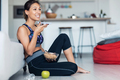 Sporty young woman eating a bowl of muesli while using mobile phone sitting on the floor at home. - PhotoDune Item for Sale
