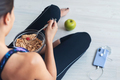 Sporty young woman eating a bowl of muesli sitting on the floor. Health care concept. - PhotoDune Item for Sale