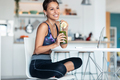 Sporty woman drinking detox juice while working with laptop after exercises in the kitchen at home. - PhotoDune Item for Sale