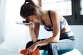 Sporty woman using mobile phone after session of exercises while sitting on fitness ball at home. - PhotoDune Item for Sale