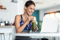 Sporty woman having online video call via laptop while drinking detox juice in the kitchen at home. - PhotoDune Item for Sale