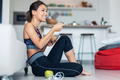 Sporty young woman eating a bowl of muesli while listening music sitting on the floor at home. - PhotoDune Item for Sale