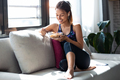 Sporty young woman eating a bowl of muesli while listening music sitting on the couch at home. - PhotoDune Item for Sale