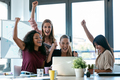 Four happy smart business women work with laptops while celebrating a victory in a coworking space - PhotoDune Item for Sale