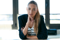 Smart beautiful young businesswoman looking at camera sitting in the office. - PhotoDune Item for Sale