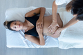 Beautiful young physiotherapist woman massaging tummy on pregnant woman on a stretcher at home. - PhotoDune Item for Sale