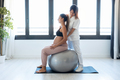 Physiotherapist helping pregnant for doing exercises with ball preparing for childbirth at home. - PhotoDune Item for Sale
