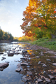 Low angle view of river in northern Michigan with rocks by trees in fall color - PhotoDune Item for Sale