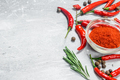 Ground pepper in a glass bowl and fresh red pepper with rosemary. - PhotoDune Item for Sale