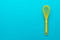 Top View Of Yellow Plastic Whisk Over Turquoise Blue Background With Copy Space - PhotoDune Item for Sale