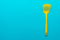 Top View Of Yellow Slotted Spatula On Turquoise Blue Background With Copy Space - PhotoDune Item for Sale