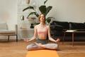 fitness female meditating in lotus pose at home - PhotoDune Item for Sale
