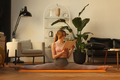 fitness female sitting in gymnastic split and reading book at home interior - PhotoDune Item for Sale