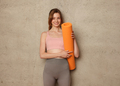 fitness female with exercise mat near concrete wall look at camera - PhotoDune Item for Sale