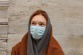 redhead female with face mask and scarf near conrete wall, close up portrait - PhotoDune Item for Sale